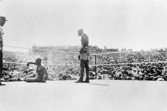 Jack Johnson standing over his opponent in the ring